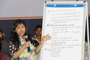 Participant summarizing her roundtable's discussions on agriculture, nutrition, and gender